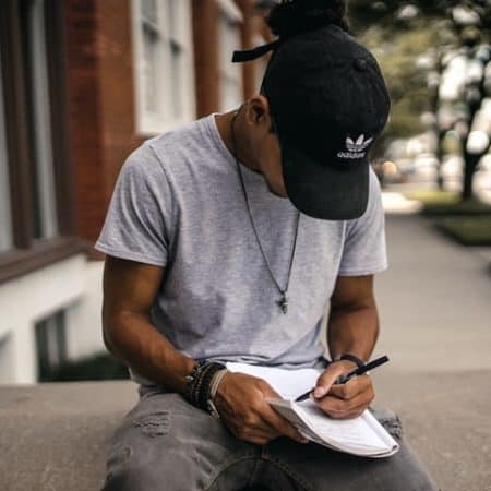 IELTS essay tips proofread Writing guy sitting on wall writing with pen and paper
